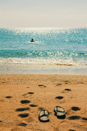 the swimmer left his Slippers and bathes in the sea 写真素材