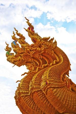 chiangmai: Head of golden Naga in blue sky Stock Photo