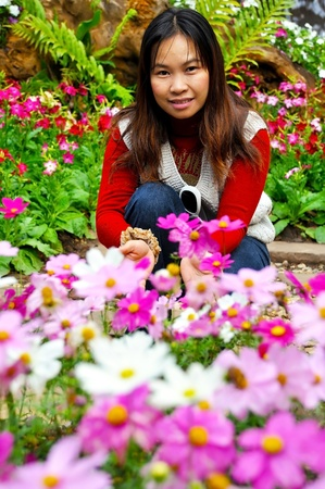 Asian woman smelling a flower in the garden