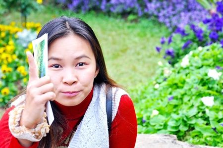 Asian woman smelling a flower in the garden photo