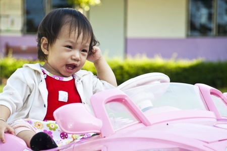 A little baby girl in Car Toy pink color photo