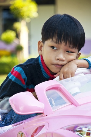 A little Boy in Car Toy pink color Stock Photo - 11710644