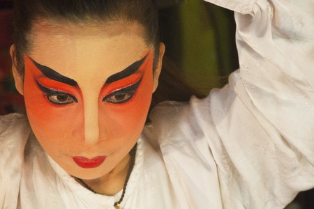 Chinese opera actress is painting mask on her face before the performance