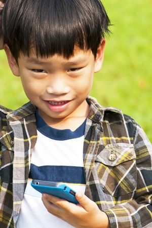 Asian little boy playing and calling Smart-phone Stock Photo - 12950867