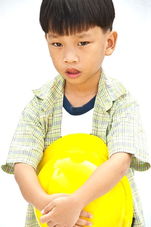 Asian Baby boy in yellow helmet holding hammer - isolated on white background photo