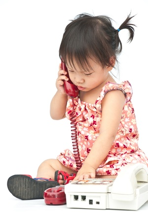 Baby dialing old beige phone calling mom isolated on white photo