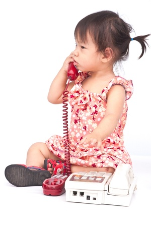 Baby dialing old beige phone calling mom isolated on white Foto de archivo