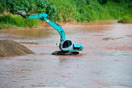 Excavator loader at river with raised bucket over blue sky Stock Photo - 13750997