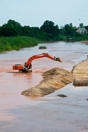 Excavator loader at river with raised bucket over blue sky photo