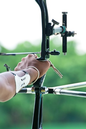 An archer with bow takes aim at a target during competition photo