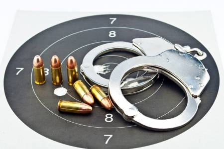 9mm Luger Ammunition and Handcuffs on target Stock Photo - 14763899