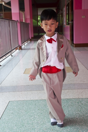 Little boy with brown tuxedo and red bow tie photo
