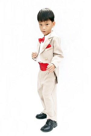 Little boy with brown tuxedo and red bow tie on white background photo