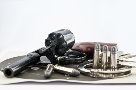 handgun revolver and police handcuff with bullets on white background Stock Photo - 15408749