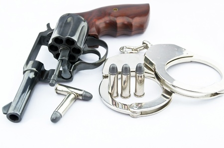handgun revolver and police handcuff with bullets on white background Stock Photo - 15408750