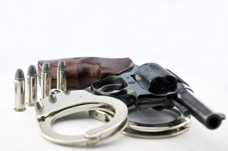wrist cuffs: handgun revolver and police handcuff with bullets on white background