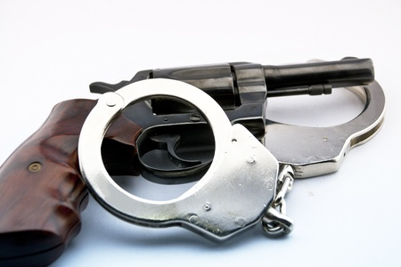 handgun revolver and police handcuff on white background Stock Photo - 15408755