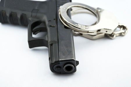 9-mm handgun automatic and police handcuff on white background Stock Photo - 15423830