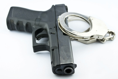 9-mm handgun automatic and police handcuff on white background Stock Photo - 15423829