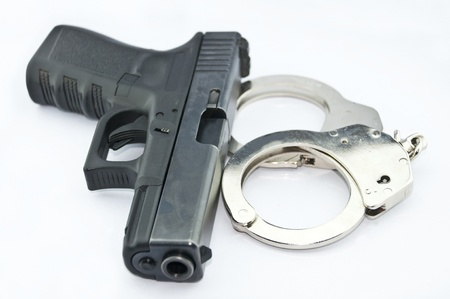 9-mm handgun automatic and police handcuff on white background Stock Photo - 15423831