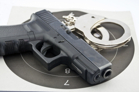 9-mm handgun automatic and police handcuff on white background Stock Photo - 15423832