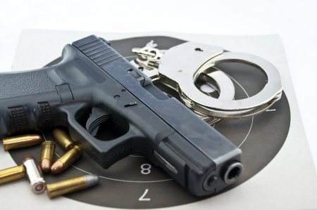 9mm: 9-mm handgun automatic and police handcuff with bullets  on white background