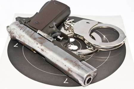 9-mm handgun automatic and police handcuff on white background Stock Photo - 15423835