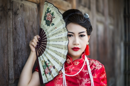 Chinese girl in traditional Chinese cheongsam blessing photo