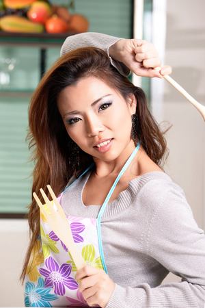 Happy asian woman cooking in the kitchen photo