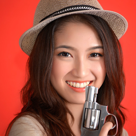 Young asian cute woman with handgun revolver photo