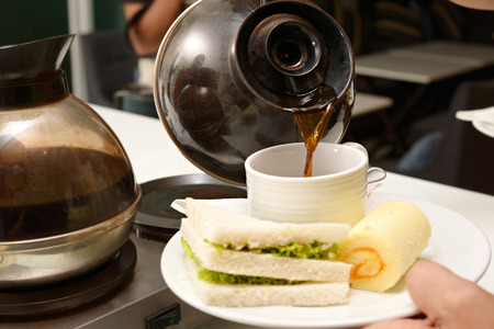 sanwich: Hot coffee in white cup with sanwich ham cheese and sweetmeat