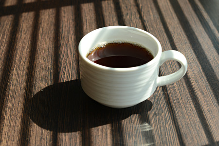 Hot Coffee cup on table near windows photo