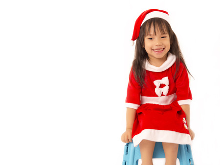 Asian little girl in red santa hat on white background photo