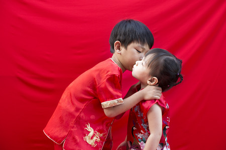 China boy and girl  in traditional Chinese red Tang suit greeting photo