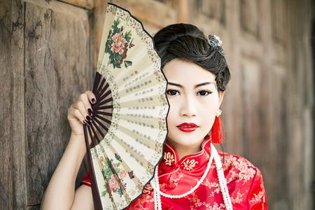 중국 여자 빨간 드레스 전통 치파오, 오래 된 나무로되는 문을 가까이 초상화
