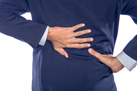 low back pain: Backache concept bending over in pain with hands holding lower back Stock Photo