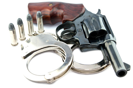 restraints: black revolver handgun with bullets isolated on isolate background. (gun target firearms shoot sights violence)