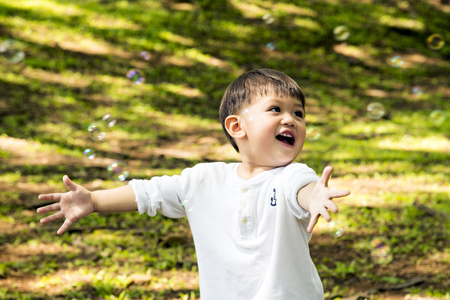 Beautiful baby boy one-year-old crawling, smiles and laughs in fallen leaves. Toddler have fun outdoor in green park rainy season