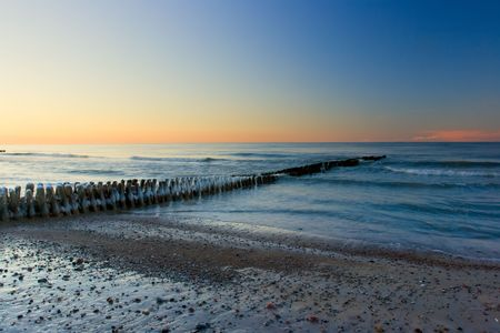 The iced over breakwater on a decline, washed by northern sea photo