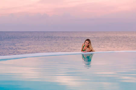 A young girl in a green swimsuit, at dawn by the sea pool, calmly and relaxed looking at her reflection in the water. Pink clouds in the background.