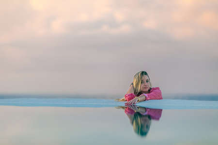 A young girl in a red shirt, at dawn by the sea pool, calm and relaxed looking at the reflection in the water. Pink clouds in the background. Banque d'images