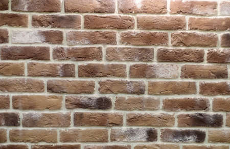 Wall with brickwork under the old destroyed brick of light beige. White mortar, texture, close-up.