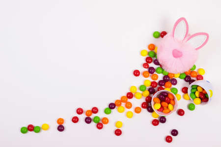 Easter concept, candy pills, egg, pink bunny head toy on white background. Place for text Imagens