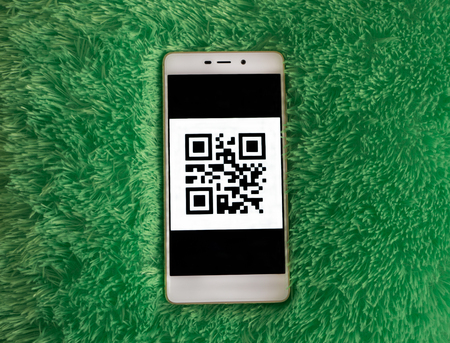 Smart phone with barcode on the screen. Turquoise artificial soft nap background