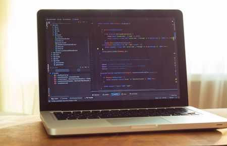 Php coding on the monitor (web developing). Laptop with code on table, working place