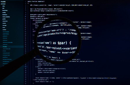 Macro code of web site under magnifying lens on the dark blue background