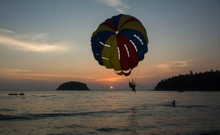 Two men landing on paraseiling on sunset, extreme sports, Phuket, Thailand