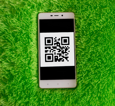 Smart phone with qr code on the screen. Green artificial soft nap background Stock Photo