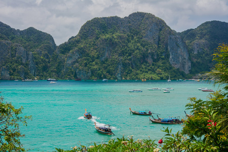 Turquoise Andaman sea, long-tail boats and islands through green leaves. Landscape background