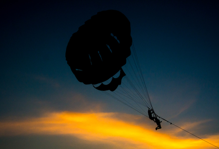 Silhouette of Parasailing at Kata beach with sunset background, extreme sports, Phuket, Thailand